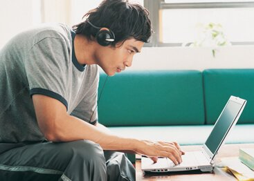 teen boy wearing headphones while working on laptop