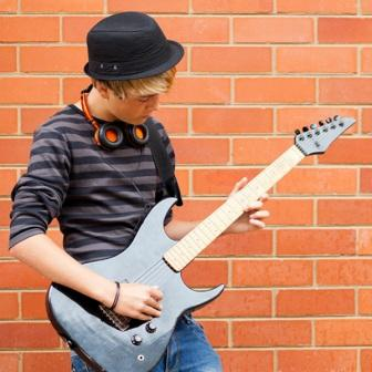 teen boy playing the electric guitar
