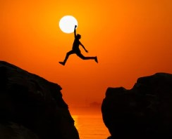 teen boy leaping across rock cliffs at sunset
