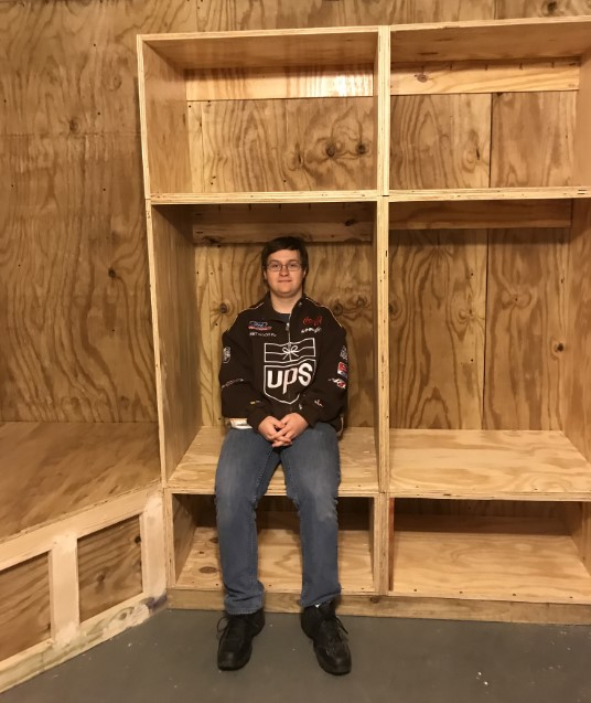 teen male showing custom built storage lockers for homeless shelter