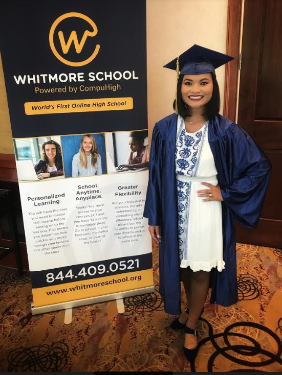 Avery standing next to Whitmore School Banner